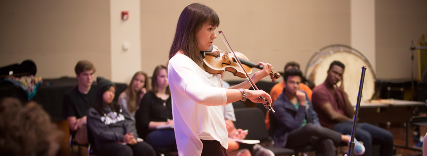 Ariana Kim playing violin for students