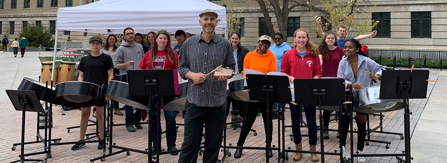 Smiling students play steel drums on an outdoor plaza