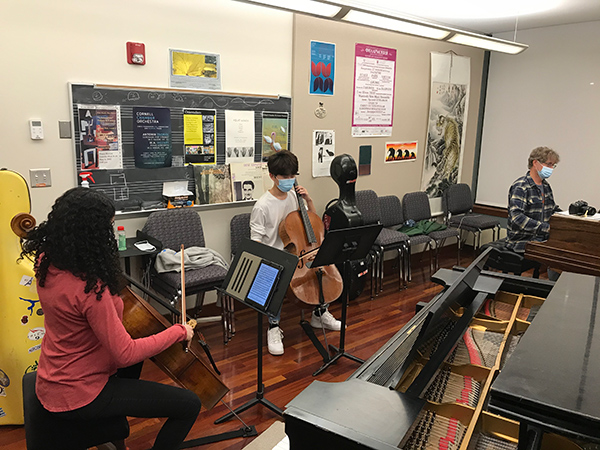 Two cellists and pianist rehearse with masks and distancing