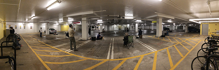 Musicians rehearse socially distanced in a parking garage