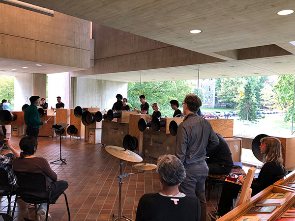 Performers play unusual instruments in a museum lobby