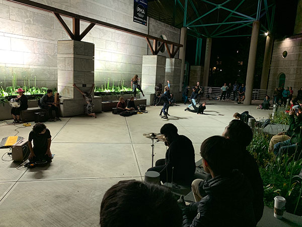 Students play music and dance on an outdoor plaza