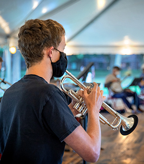 Student plays trumpet with a mask in a tent