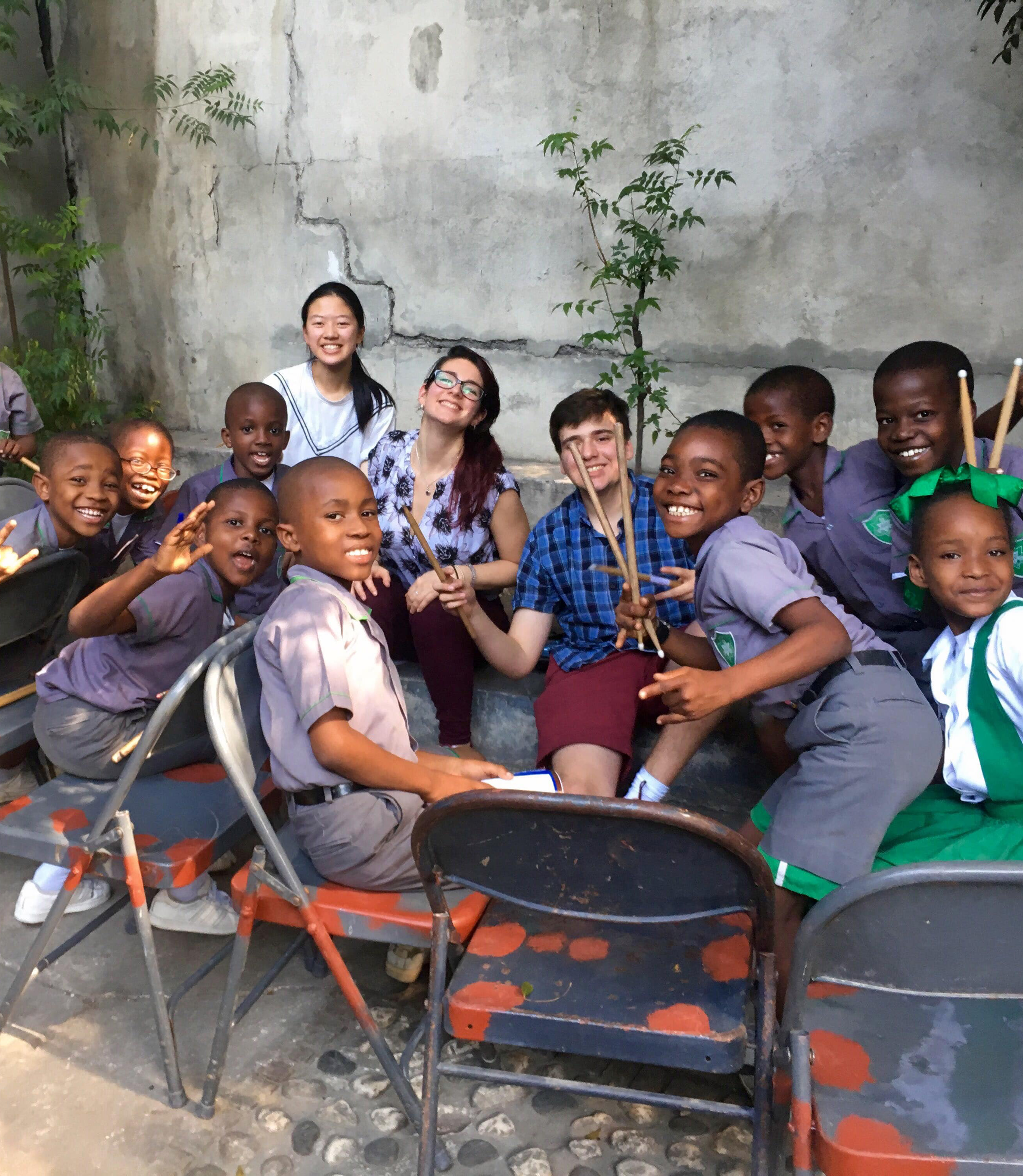 Cornell Wind Symphony members playing percussion with Haitian students