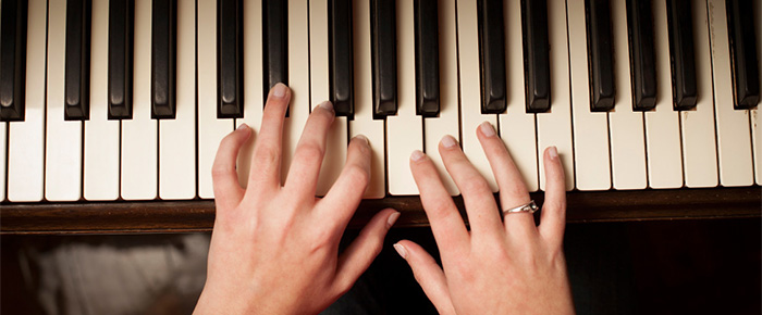 Hands playing piano keyboard