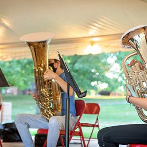 Tuba player rehearses in a tent outdoors