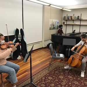 A violinist, cellist, and pianist rehearse with masks and distancing