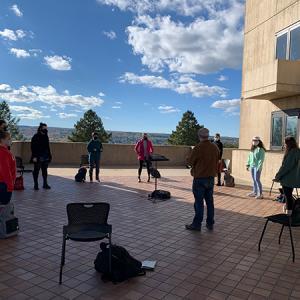 A socially distanced, masked vocal ensemble rehearses outdoors